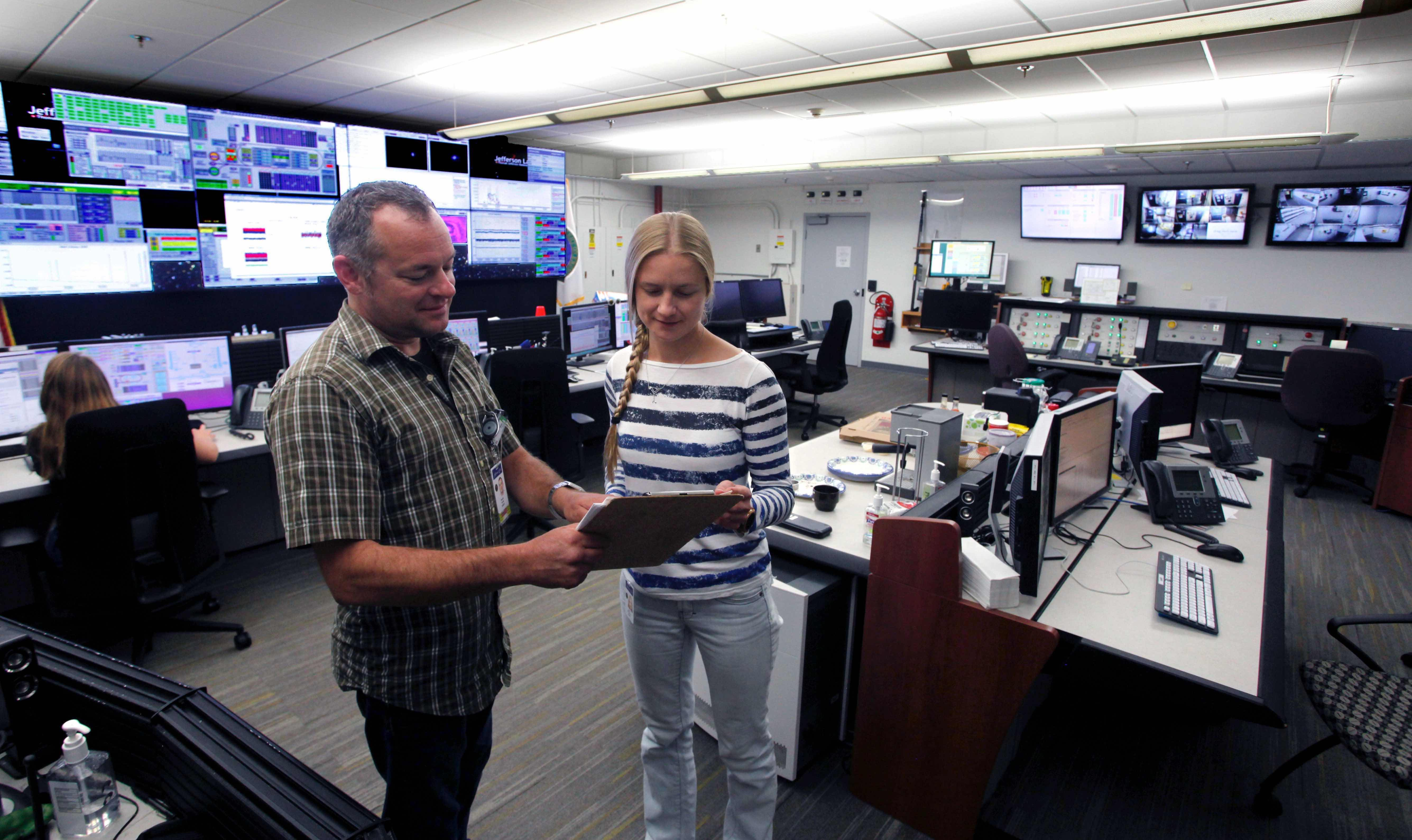 Anna Sabalina (left) confers with an accelerator operator in the CEBAF control room.